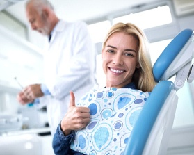 woman smiling and giving thumbs up in dental chair