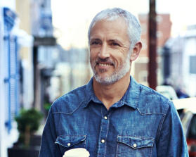 man in jean jacket holding coffee