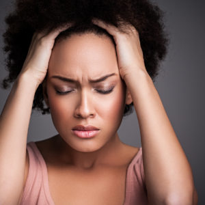 Young African woman suffering from a terrible headache.