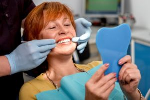 A woman viewing her dental implants.