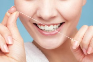 woman smiling while flossing teeth